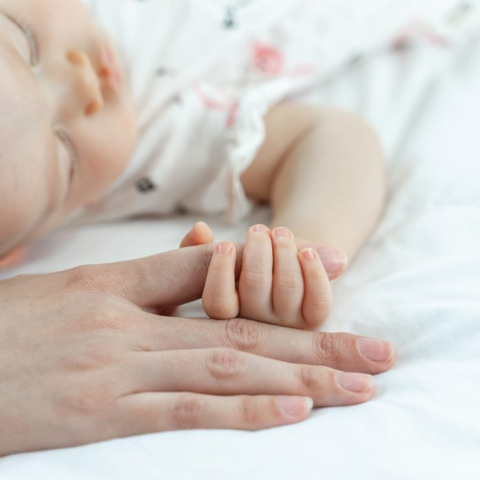 The newborn baby sleeps and grabs the mother's finger